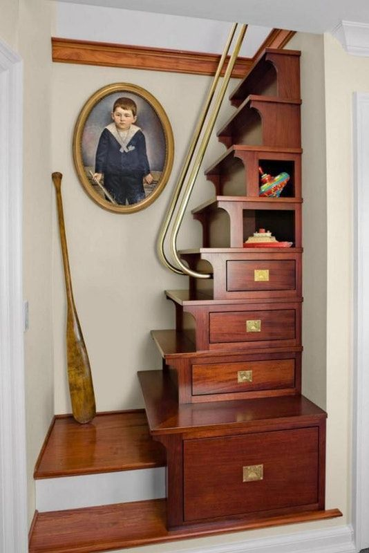 storage stairs in dark brown wooden with golden metallic handrails