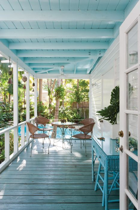 terrace with blue wooden floor, white wooden wall, blue wooden ceiling, rattang chairs with round glass table