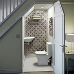 Toilet Under The Stairs With White Toilet, White Sink, White Floor, Bold Brown Wallpaper In One Side