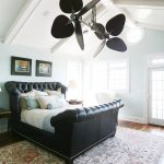 Unusual Ceiling Fans Black Leathered Bed Tufted Headboard Colorful Bedding Patterned Area Rug Black Framed Artwroks Nightstands Table Lamps Glass Windows