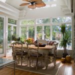 Unusual Ceiling Fans Wooden Dining Table Wooden Chairs Patterned Cushions Small Area Rug White Framed Windows And Doors Glass Roof