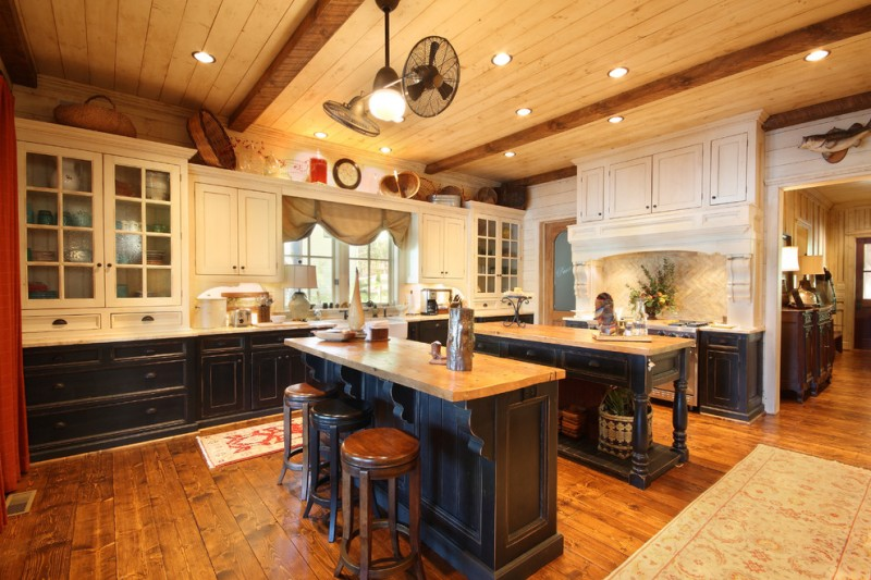 unusual ceiling fans wooden floor black double island white kitchen cabinet white backsplash white countertop recessed light window stovetop stools