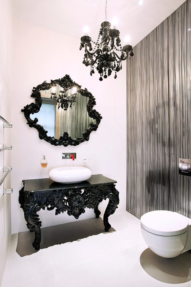 white powder room with white toilet, flooring, wall, dark accented table and mirror, one side of wall in silver