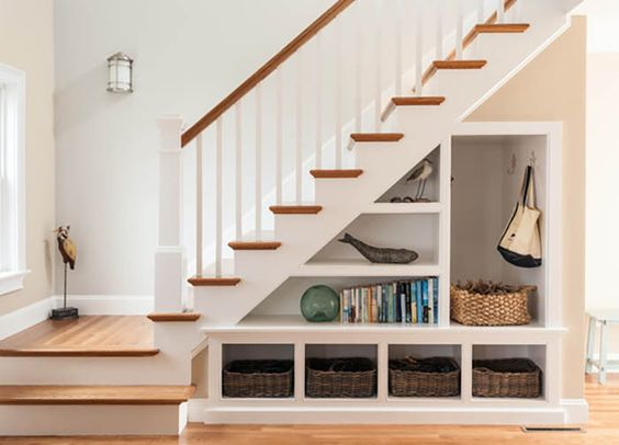 white wooden opened shelves under the stairs