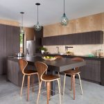 Wood Stool Blue Glass Pendnat Lights Dark Brown Wooden Cabinets Beige Walls Dark Brown Countertop Island Sink Stovetop Grey Floor