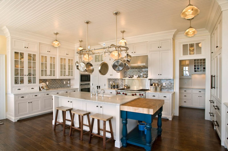 wood stool white kitchen cabinets white island stainless steel hanging pans grey subway backsplash stovetop oven sink pendant lamps white countertops
