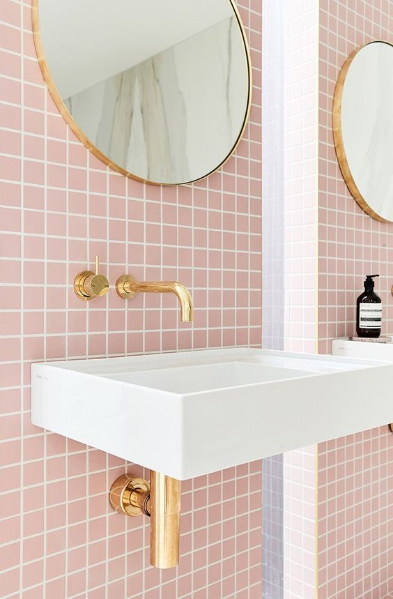 bathroom sink with pink square backsplash, golden faucet, golden framed round mirror