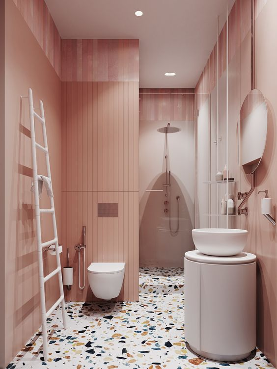 bathroom with pink long tiles on the wall, white toilet, white sink with round white cabinet, round mirror, terazzo floor