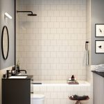 Bathroom With White Square Tiles On The Walls, Floor, White Bath Tub, White Toilet, Wooden Stool, Dark Brown Sink With Round Mirror