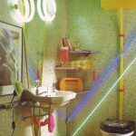 Bathroom With Yellow Floor, White Toilet, White Sink With Colourful Ornament, Wall Shelves, Round Lamp, Mirror