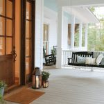 Black Wooden Hanging Sofa With Pillows On White Wooden Porch