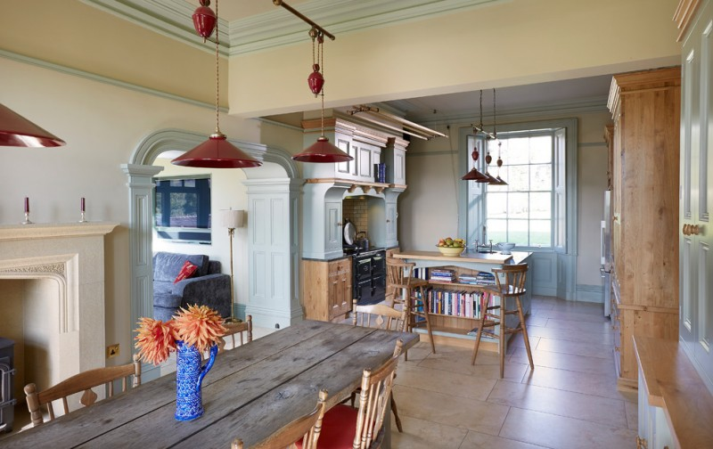 farmhouse tables red pendant lamps wooden chairs with red cushion beige floor tile fireplace beige mantel floor lamp grey sofa white cabinets