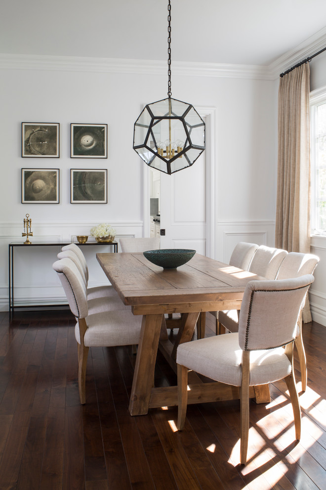 farmhouse tables woode floor white cushioned wooden chairs glass chandelier artworks console table glass window beige curtains