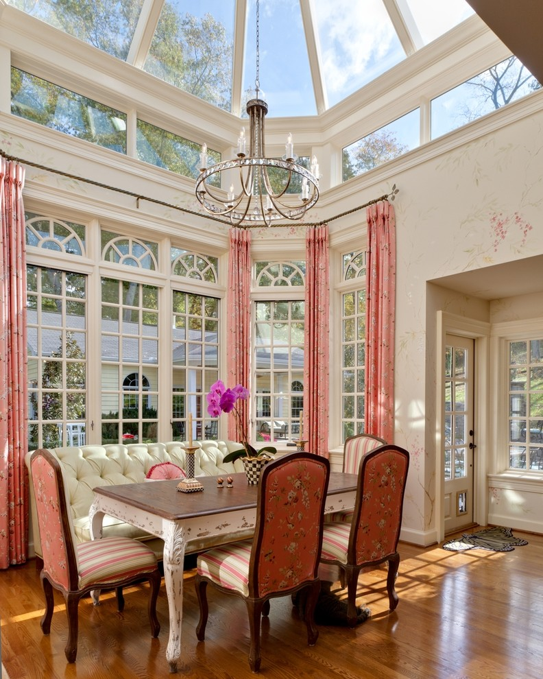 farmhouse tables wooden floor pink curtains striped pink cair white bench with tufted back chandelier white framed glass windows