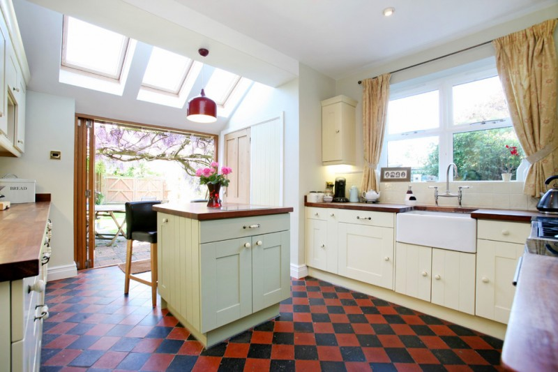 fireclay farm sink black and red floor tile small wooden island black barstools silk curtans glass wndows beige cabinet wooden countertops pendant lamp stove