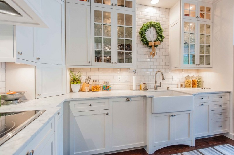 fireclay farm sink glass cabnet doors white cabinets dishwasher white subway backsplash white marble countertops stovetop recessed light kitchen mat