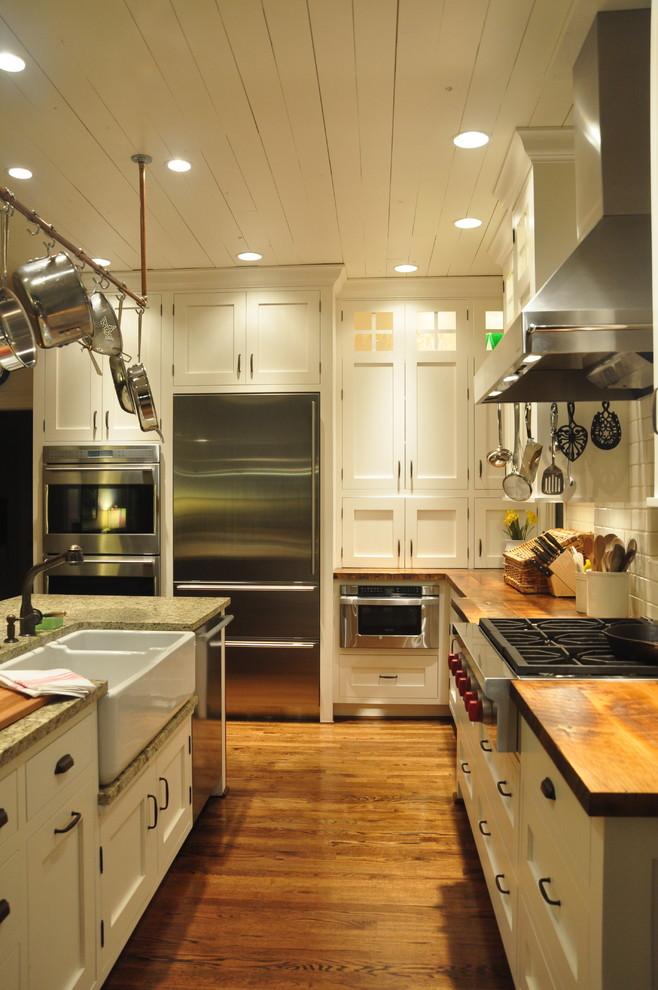 fireclay farm sink hanging pans stovetop range hood countertops island dishwasher oven white cabinet wooden floor refrigerator white backsplash