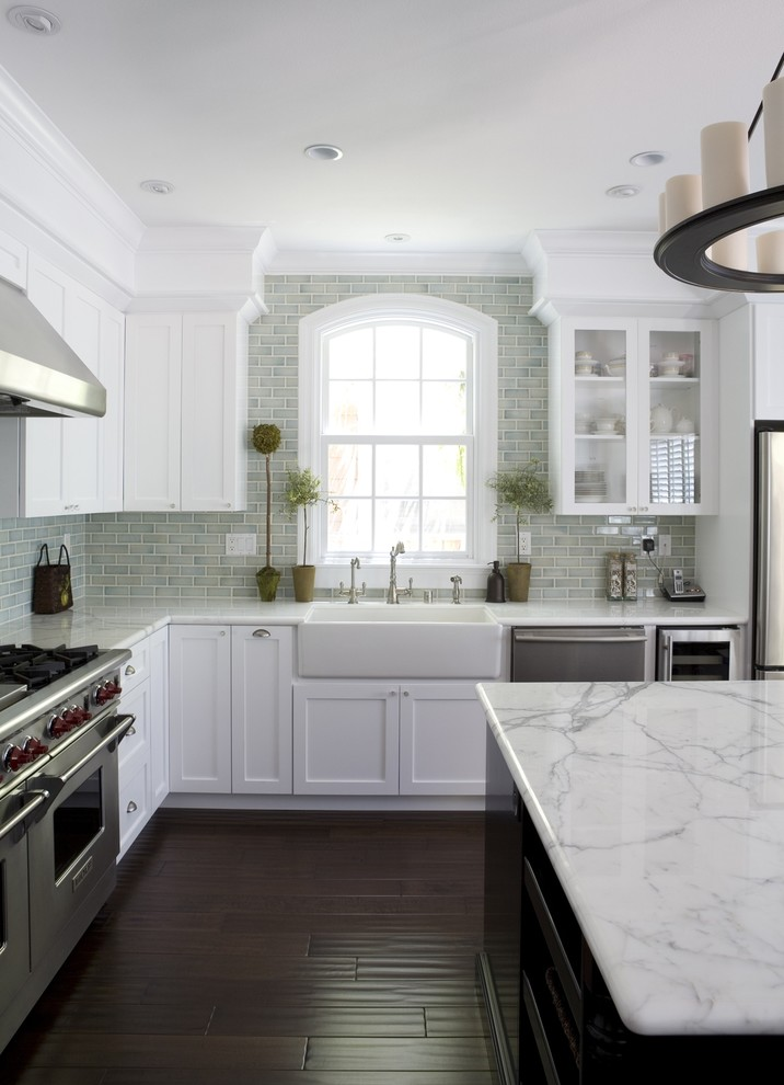 fireclay farm sink white framed glass window grey subway tile wooden floor white cabinets dishwasher stovetop rangehood marble countertop
