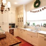 Fireclay Farm Sink White Kitchen Cabinets Windows Blinds Dishwasher Wooden And White Countertops Kitchen Mat Wooden Floor Refrigerator Chandelier