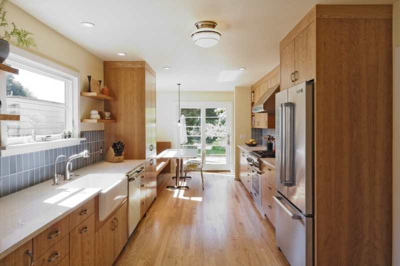 fireclay farm sink wooden floor ceiling lamp wall mounted wooden shelves stove oven refrigerator white pedestal table wooden cabinets white countertops