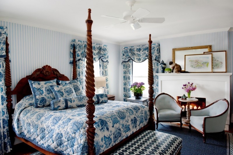 fireplace candle ideas blue and white bedding wooden canopy bed headboard bench armchairs side table white ceiling fan windows valances nightstands