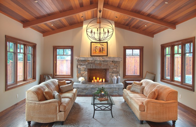 fireplace candle ideas chandelier stone fireplace beige sofas glass coffee table area rug wooden vaulted ceiling glass windows throw pillows