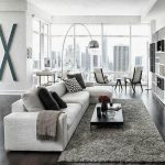 Living Room With White Wall, Black Wooden Floor, White Sofa, Black Low Wooden Coffee Table, Grey Rug, Floor Lamp