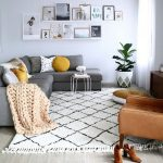 Living Room With White Walls, Grey Sofa, Brown Leather Sofa, Brown Floor Pillow, Small Round Table, White Rug
