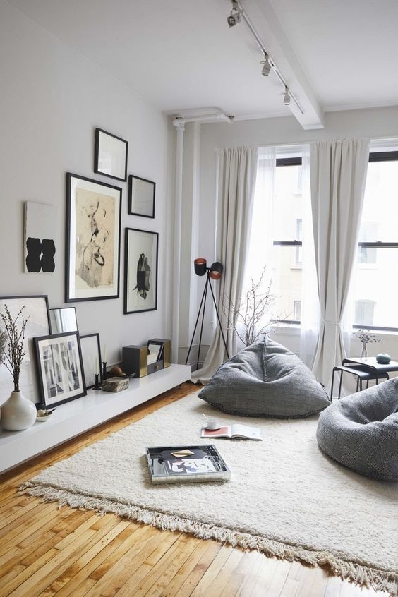 living room with white walls, wooden floor, grey rug, low white cabinet, grey bean bag, white curtain