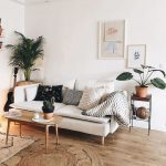 Living Room With White Walls, Wooden Floor, Round Rattan Rug, White Sofa, Brown Wooden Coffee Table, Plants
