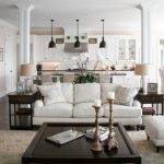 Metal End Table Black Pendant Lamps Dark Wooden Coffee Table White Sofas White Armchair White Footstool Patterned Area Rug Table Lamps