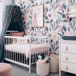 Nursery With Big Flower Wallpaper, White Baby Box, Navy Curtain, Grey Rug, Pink Ottoman, White Wooden Cabinet, White Rattan Basket