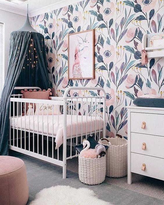 nursery with big flower wallpaper, white baby box, navy curtain, grey rug, pink ottoman, white wooden cabinet, white rattan basket