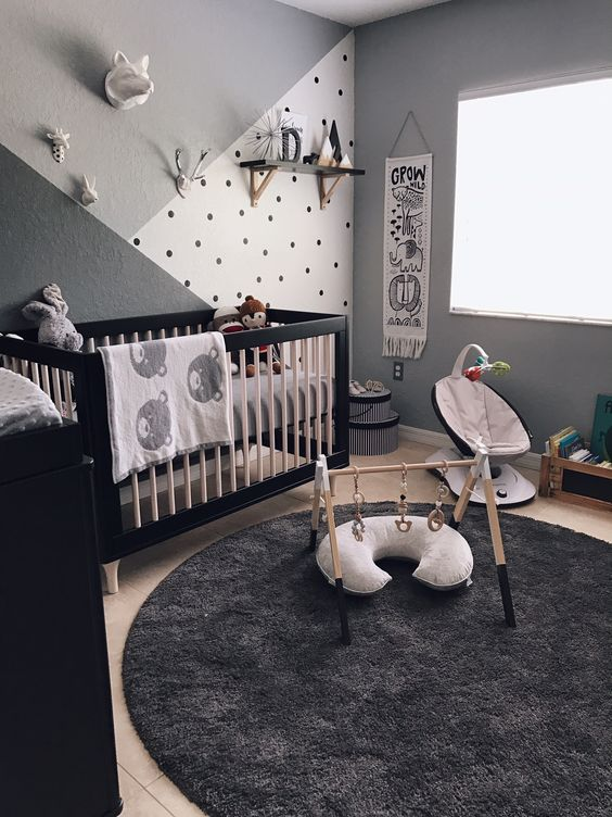 nursery with grey wall, brown wooden floor, black round rug, black cabinet, black wooden baby box