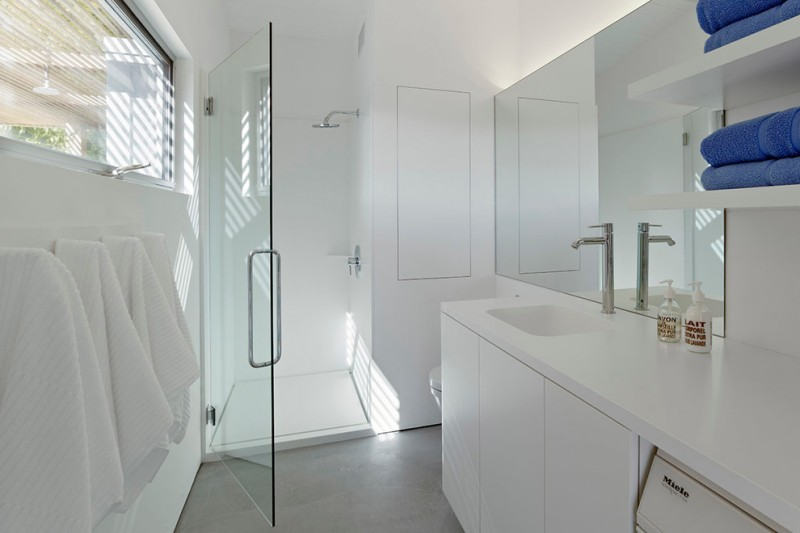 solid shower base glass shower door white flat panel vanity white top sink faucet towel hoks window shelves wall mirror