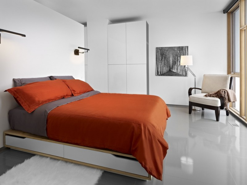 underbed storage solutions orange and grey bedding pillows black wall sconces white flat panel wardrobe white shag rug black artwork wooden armchair floor lamp grey flo