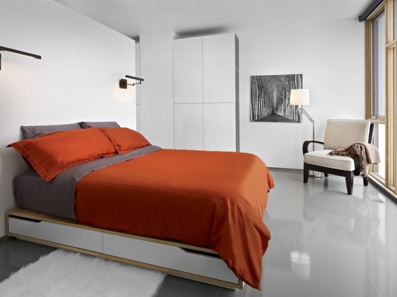 underbed storage solutions orange and grey bedding pillows black wall sconces white flat panel wardrobe white shag rug black artwork wooden armchair floor lamp grey flo