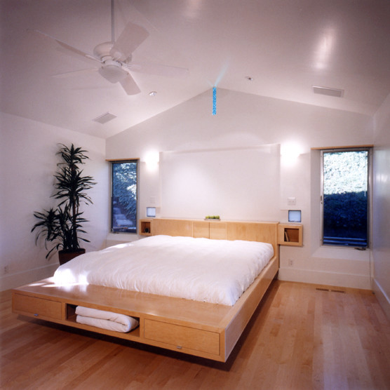underbed storage solutions white bedding built in headboard wall sconces white ceiling fan windows drawers shelf indoor plant wooden floor
