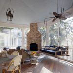 Wooden Hanging Sofa With Blue Cushion, Pillows, In Sunroom Near The Fireplace