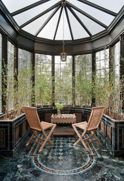 a circle sun room with large windows circled the room, plants curtain, lamp, wooden foldable chairs