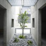 A Corner Space Wth Grey Wall, Grey Concrete Floor, Grey Stones On The Floor, Some Plants, Wired Ceiling