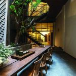 A High Space With Tree Near The Stairs, A Long Wooden Table With Wooden Chairs Along The Wall