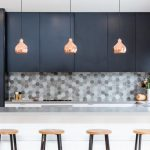 Backsplash Texture Hexagonal Backsplash Rustic Gold Pendant Lamps Blue Cabinets White Island White Countertops Glass Windows Wooden Stools Sink Stovetop