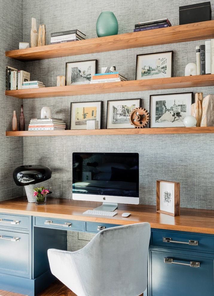 bamboo desk top black drawers pictures frames built in wooden shelves grey mosaic wall wooden floor grey chair books decorations