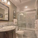 Bathtub Cartridge Wall Sconce Grey Wall And Floor Tiles Glass Shower Door Backsplash Curved Wooden Vanity Sink Wall Mirror