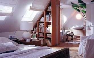 bedroom with vaulted ceiling, slanting in one side, slanting bookshelves, windows on slanting ceiling, white chair, rattan bed, bathroom