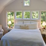 Bedroom With Whtie Wall, Small Windows, Ceiling Fan, White Shed Vaulted Ceiling, Whtie Couch, White Side Tables With White Table Lamp, Bed With White Linen