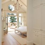 Bedroom With Wooden Floor, Off White Rug, White Bed, White Bench, Vaulted Ceiling, Chandelier