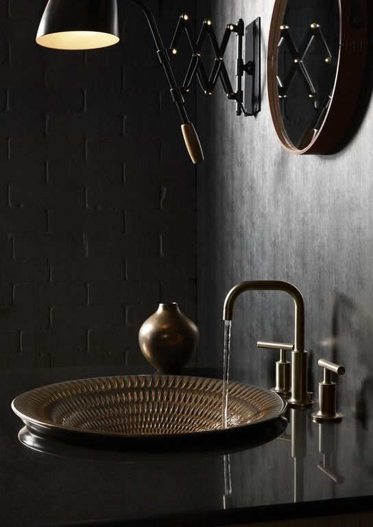 black shiny and smooth marble of sink with bronze sink, bronze faucet, black shiny wall lamp, round wall mirror