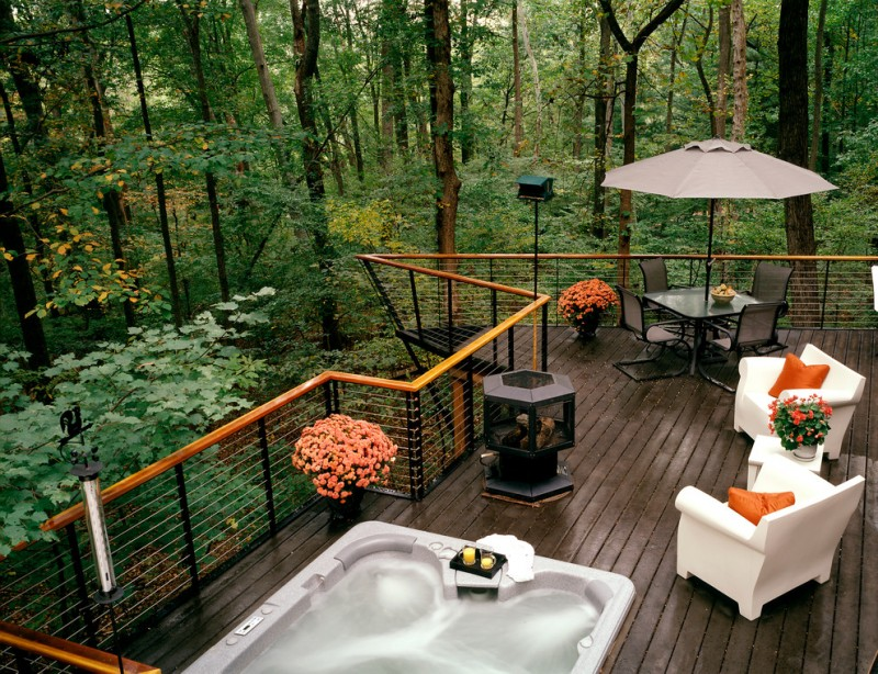 cable railing deck hot tub outdoor tub outdoor umbrella black chairs pedestal table white chairs orange pillows firepit